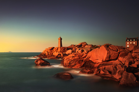 ploumanac'h: Ploumanach Mean Ruz lighthouse red sunset in pink granite coast, Perros Guirec, Brittany, France. Long exposure. Stock Photo