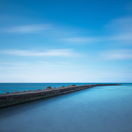 crepuscle: Concrete pier, rocks and sea on sunset. White beach, Tuscany, Italy. Long Exposure.