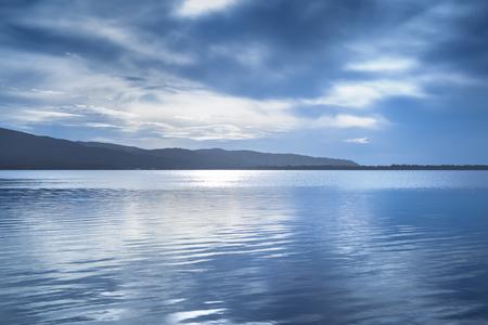 Sunset blue landscape. Orbetello lagoon with reflection, Argentario, Tuscany, Italy.