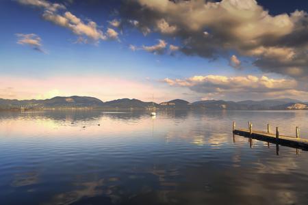 sunset sky: Wooden pier or jetty and on a blue lake sunset and cloudy sky reflection on water. Versilia Massaciuccoli Lake, Tuscany, Italy.