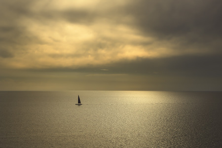 voile: Ocean sea sunset view and black sail boat. Mediterranean sea. Tuscany, Italy