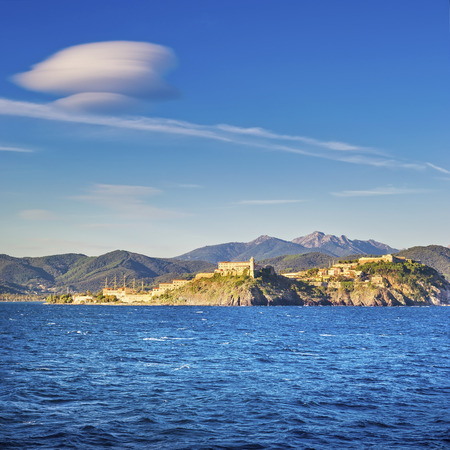 lenticular cloud: Elba island, Portoferraio village skyline and lenticular cloud from a ferry boat. Tuscany, Italy.