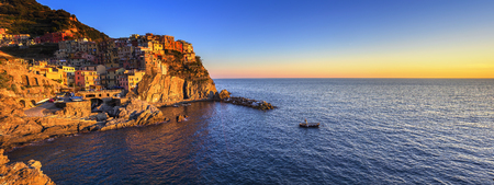 crepuscle: Manarola village on cliff rocks and sea at sunset., Seascape in Five lands, Cinque Terre National Park, Liguria Italy Europe. Panoramic view.