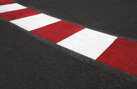 formula one: Texture of motor race asphalt and red white curb. Close up on Monaco Montecarlo Grand Prix street circuit Stock Photo