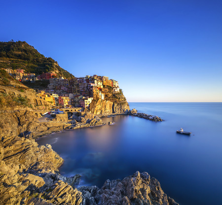 crepuscle: Manarola village on cliff rocks and sea at sunset., Seascape in Five lands, Cinque Terre National Park, Liguria Italy Europe. Long Exposure