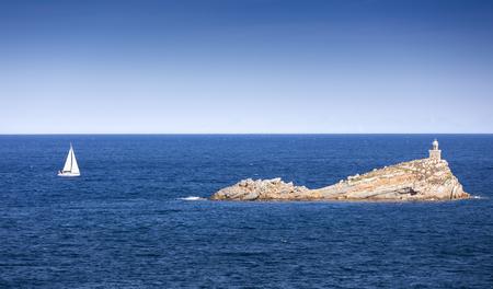sail boat: Elba island, Portoferraio Scoglietto little rock, boat and lighthouse. Tuscany, Italy. Stock Photo