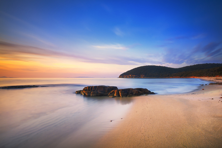 Sunset Cala Violina bay beach in Maremma, Tuscany. Travel destination in Mediterranean sea. Italy, Europe. Long Exposure. Stock Photo