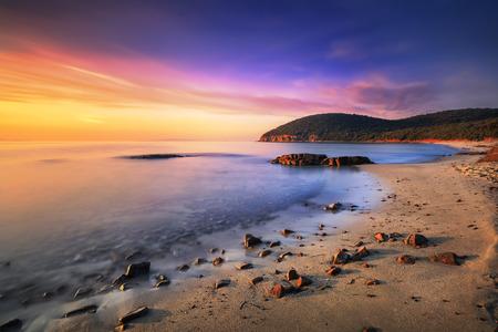 일몰 Cala Violina 베이 해변에서 Maremma, 토스카. 지중해 바다에서 여행 목적지입니다. 이탈리아, 유럽. 긴 노출. 스톡 콘텐츠