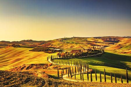 風景: トスカーナ、クレテ ・ セネージ農村の日没の風景。田舎ファーム、糸杉の木、雲、太陽の光を緑のフィールド。イタリア、ヨーロッパ。