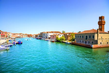 venezia: Murano glass making island, water canal, bridge, boat and traditional buildings. Venice or Venezia, Italy, Europe.