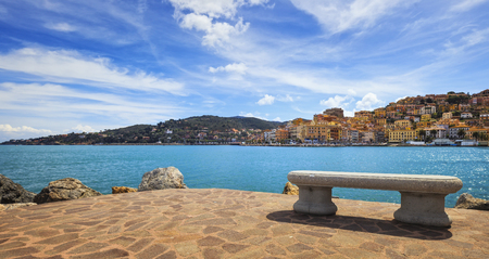 Bench on seafront in Porto Santo Stefano harbor, Monte Argentario, Tuscany, Italy.