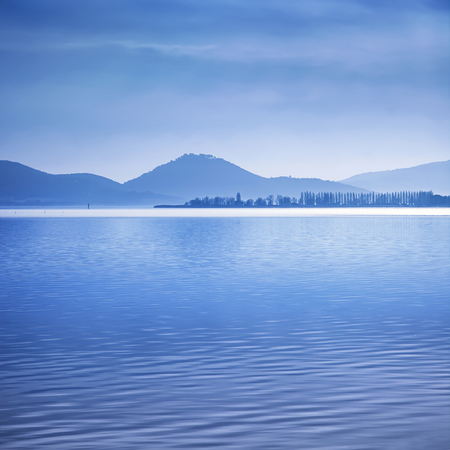 italy background: Water surface and poles in a blue morning on the Trasimeno lake, Umbria Italy. Hills on background.