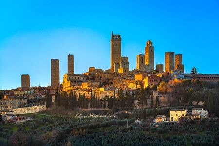 San Gimignano town skyline and medieval towers sunset in blue hour. Italian olive trees in foreground. Tuscany, Italy, Europe.