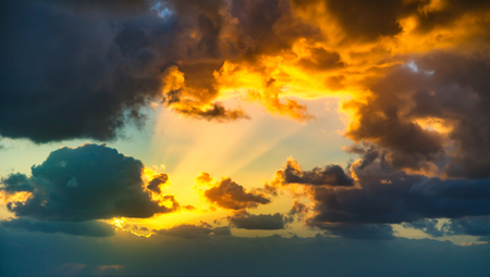 Dramatic sunset sky with yellow, blue and orange approaching thunderstorm clouds.