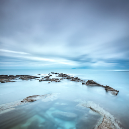 blue cloudy sky: Dark rocks in a blue ocean under cloudy sky in a bad weather. Long exposure photography