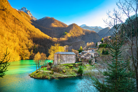 Isola Santa medieval village, church, lake and Alpi Apuane mountains. Garfagnana, Tuscany, Italy Europe Standard-Bild