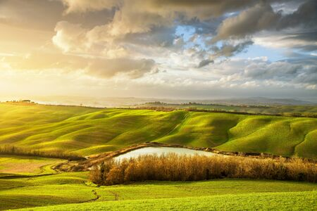Tuscany misty panorama, lake, rolling hills, fields, meadow and trees at sunset. Italy, Europe