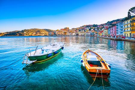 Wooden small old boats in Porto Santo Stefano seafront, italian travel destination. Monte Argentario, Tuscany, Italy.