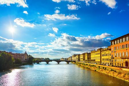 Florence or Firenze, Ponte Santa Trinita medieval Bridge landmark on Arno river, sunset landscape. Tuscany, Italy.