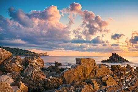 livorno: Rocks and buildings on the sea at sunset. Livorno coast, Tuscany riviera, Italy, Europe.