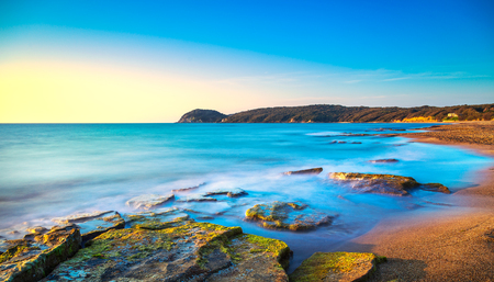 Baratti beach bay, travel destination, headland hill, rocks and sea on sunset. Maremma Tuscany, Italy, Europe. Long Exposure