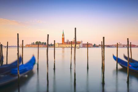 Venice lagoon at sunrise, San Giorgio Maggiore church, gondolas and poles. Italy, Europe.