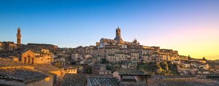 シエナの夕日のパノラマのスカイライン。マンギアタワーとドゥオーモ大聖堂のランドマーク。トスカーナ、イタリア。 写真素材