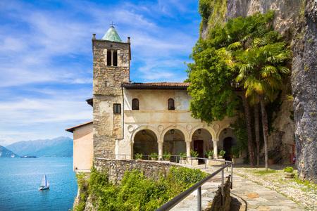 Hermitage or Eremo of Santa Caterina del Sasso medieval roman catholic monastery. Leggiuno Maggiore lake, Lombardy Italy, Europe. Long Exposure. Stock Photo
