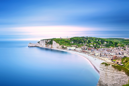 Etretat village and its bay beach, aerial view from cliff. Normandy, France, Europe. Long exposure photography