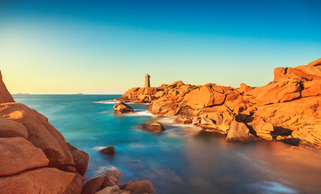Ploumanach Mean Ruz lighthouse red sunset in pink granite coast, Perros Guirec, Brittany, France. Long exposure. Reklamní fotografie