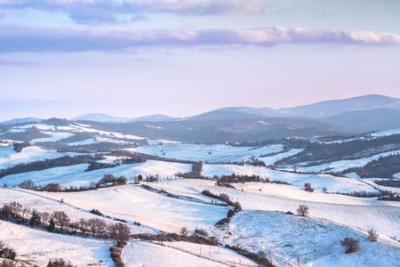 Snow in Tuscany, winter panorama at sunset. Radicondoli, Siena, Italy Europe.