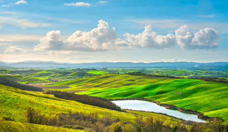 Tuscany landscape, small lake, green and yellow fields in Crete Senesi. Italy, Europe.