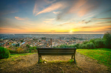 Park bench and Pietrasanta aerial view from Rocca di Sala fortress at sunset. Versilia Lucca Tuscany Italy Europe