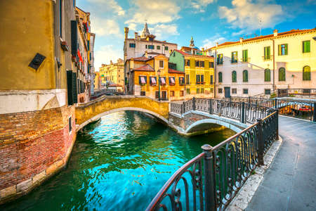 Venice sunset cityscape, water canal, double bridge and traditional buildings. Italy, Europe. 스톡 콘텐츠