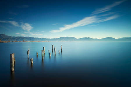 Wooden pier or jetty remains and lake at sunrise. Long Exposure. Massaciuccoli lake. Torre del Lago Puccini, Versilia, Tuscany, Italy, Europe