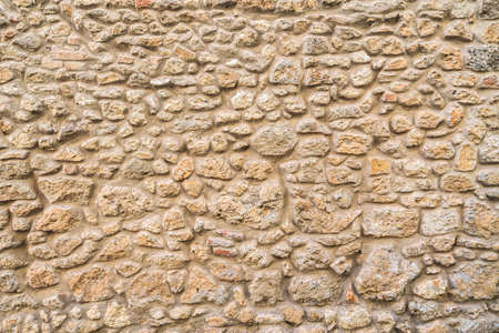 Exposed stone wall background, pattern, texture in Tuscany. Italy