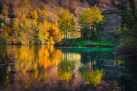 Autumn foliage. Woods and lake of Isola Santa old village. Garfagnana, Tuscany, Italy, Europe.