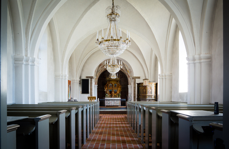 reredos: Inside a white church in the countryside, with an aisle of bricks, chandeliers and reredos of wood, Lackalanga, Sweden - May 6, 2015,