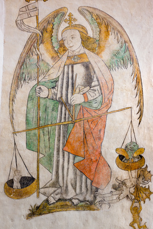 St. Michael weighing a soul, devils hanging on the other side, a fresco painting in Aarhus cathedral, Denmark - Juni 21, 2015
