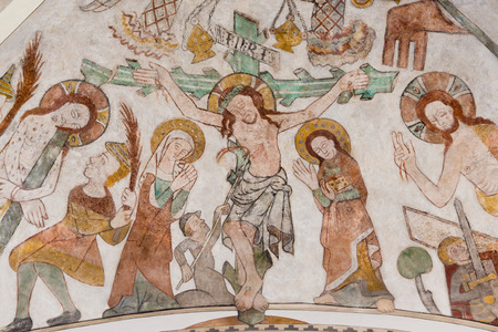The crucifixion of Jesus on Good Friday. His mother Mary and St. John standing at the cross with the heading INRI. Gothic fresco in Skibby church, Denmark - February 21, 2017