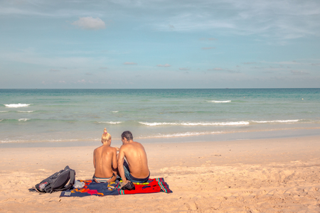 picknick: Man and woman have a picnic on a tropical beach, sitting on a blanket, Haad Rin, Koh Pangan, May 05, Thailand