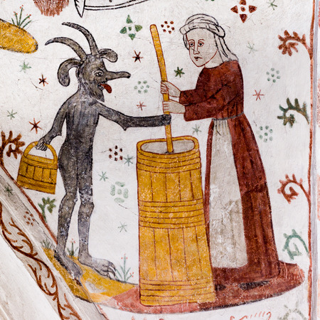 Medieval Fresco of a woman churning Butter with the Devil, Tingsted church, Denmark - April 11, 2017