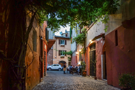 Having dinner at an outdoor italian restaurant in an narrow alley, Trastevere, Rome - May 04, 2017 Editorial