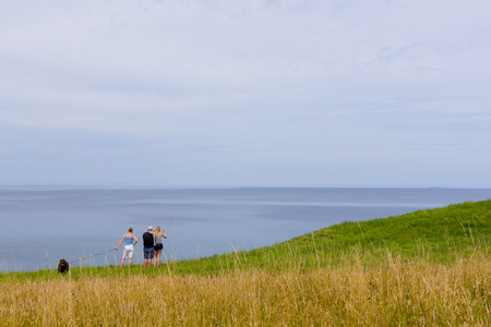 Family standing in the grass high above  the sea, Hundested, Denmark, July 10, 2017 Editorial