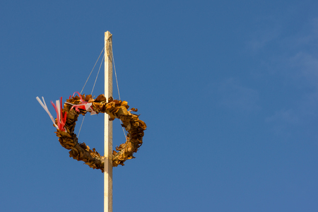 Topping out wreath flowing in the wind,  against blue sky, Holl, Denmark, August 23, 2017 Stock Photo