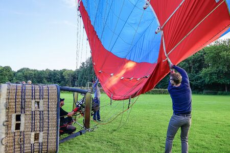 Pilot of a hot air balloon inflates the balloon with hot air, Zealand, Denmark. August 14, 2017
