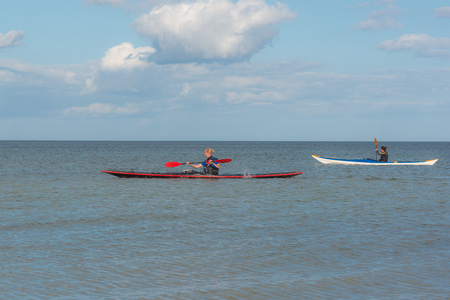 Two women are paddling a red and a white kayak in the sea,, Holl, Denmark, August 27, 2017