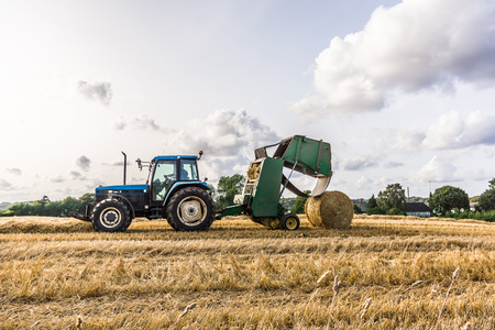 Straw Baling Machine after a tractor at work in an field in Borkop, Denmark, August 25, 2017 Editorial