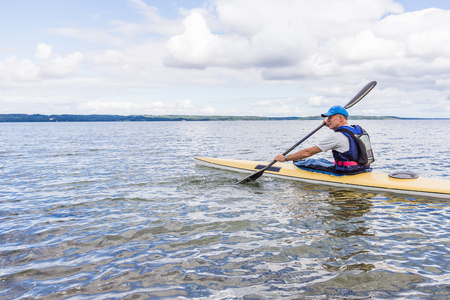 Man is paddling a yellow kayak alone in the bay, Holl, Denmark, August 27, 2017