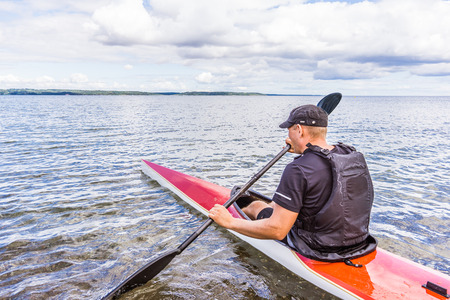 A man kayaking alone in the bay, Holl, Denmark, August 27, 2017 Editorial